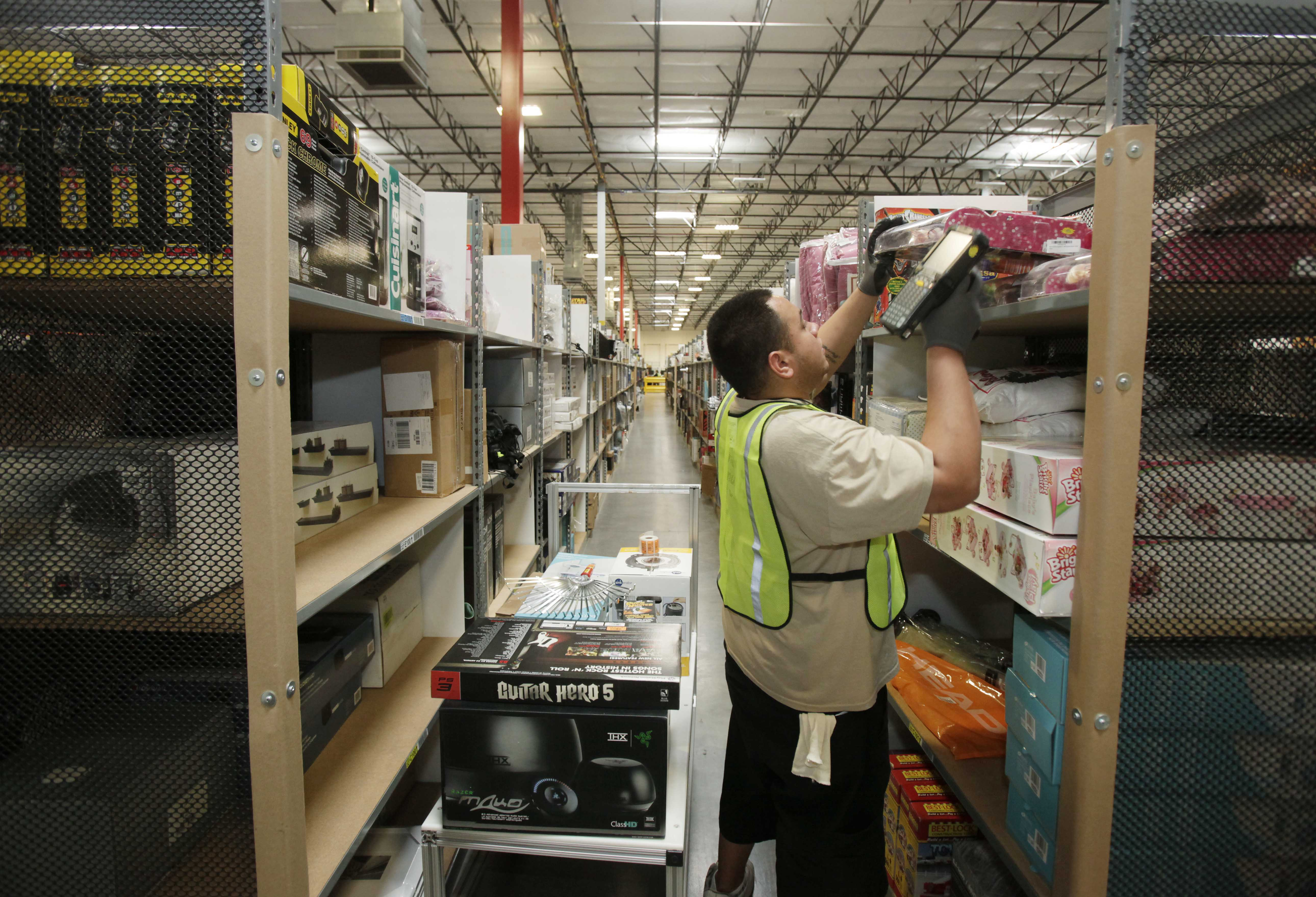 In this November 2009 file photo, Marcus Marintez pulls items for shipment inside the 800,000 sq. ft. Amazon.com warehouse in Goodyear, Ariz. (Ross D. Franklin/AP)