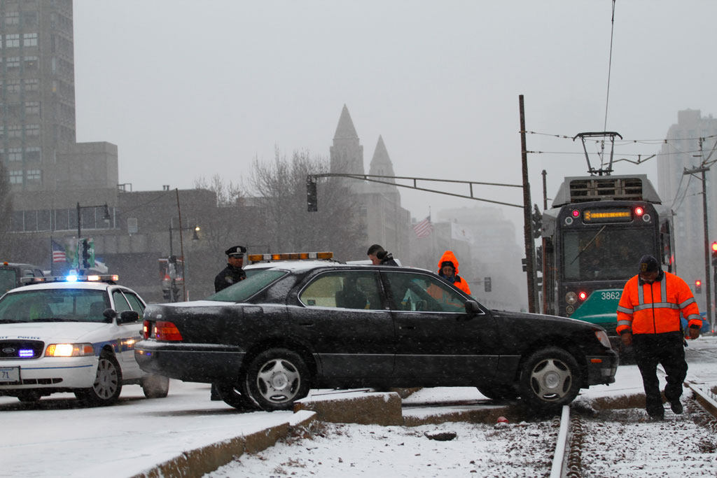 A car traveling west on Commonwealth Avenue, near the BU Bridge, skid on ice and ended up right in front of a Green 'B' Line MBTA train. (Andrew Phelps/WBUR)