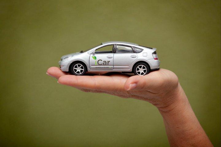 A hand holds an iCar model
