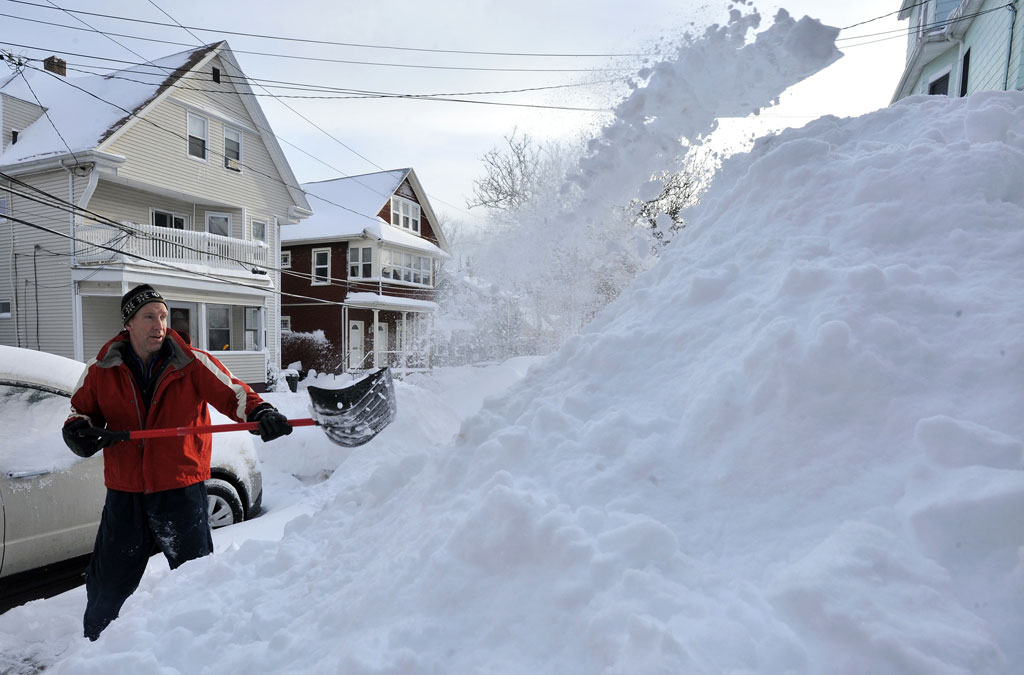 Kevin Andrew adds to the pile of snow on his front yard as he clears his driveway in Somerville on Thursday morning. (Josh Reynolds/AP)